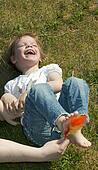 laughing child being tickled under the feet with a colorful